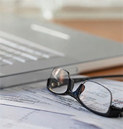 Image of laptop on top of forms and eyeglasses beside it
